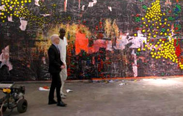 Artist Mark Bradford shows Anderson Cooper one of his pieces